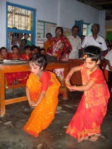 Zwei Erstklässlerinnen tanzen bei der Eröffnung der Schule